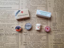 verband,  2 doosjes, zalf, pillen en leukoplast