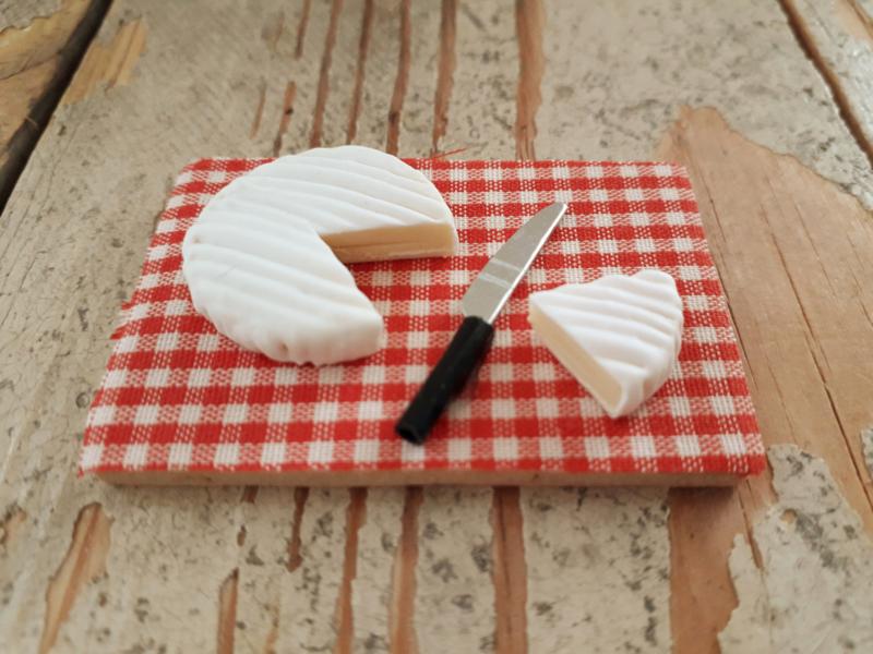 camembert kaas op plank met mes
