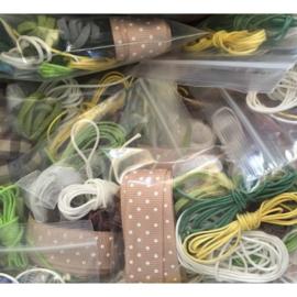 Pakketje met prachtige assortiment lintjes, veters, waxkoordjes en dergelijke.