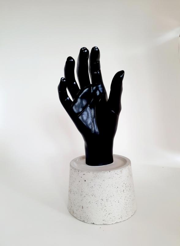 Hand op betonnen voet