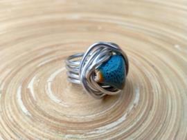 Zilverkleurige wire ring met een keramieke driehoekige kraal. Maat 19