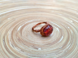 Koperkleurige wire ring met rode zilverfoil kraal. Maat 17.5