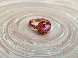 Koperkleurige wire ring met een roze facet geslepen glaskraal. Maat 18.5