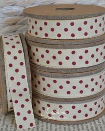 Kartonnen spoel met lint. Crème met rode stippen