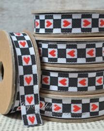 Kartonnen spoel met lint.  Zwart/wit met rode hartjes