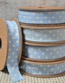 Kartonnen spoel met lint. Lichtblauw met crème stippen