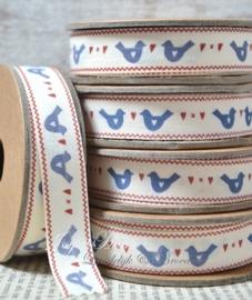 Kartonnen spoel met lint. Blauwe duifjes
