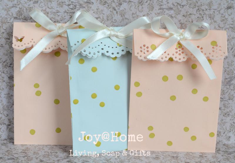 Papieren cadeauzakjes met een randpons en strikje in 2 kleuren