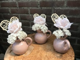 bruiloft decoratie, tafelversiering, stenen kruikjes met kunstbloemen en een hart