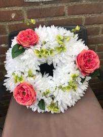 Bloemenkrans gevuld met witte chrysanten, zijde bloesem, zijde pioenrozen