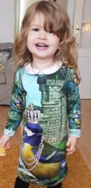 Een blij meisje met haar Meesjes jurkje.