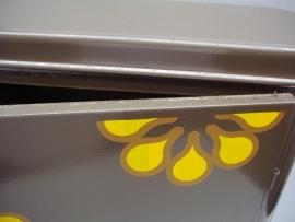 Bruin medicijnkastje met retro gele bloem.