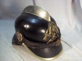 German firehelmet 1910- 1930, complete with 2 cocards. Duitse leren brandweerhelm, compleet met de 2 cocarden, binnenwerk, embleem, stormriem en zelfs de makerplaatjes.