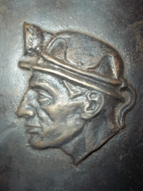 Bronze plaque of a miner wearing his typical helmet.Bronzen plaquette van een mijnwerker met zijn helm.