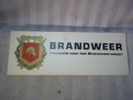 Bordje BRANDWEER inspectie voor het brandwezen met embleem, werd in de auto voor het raam gelegd.