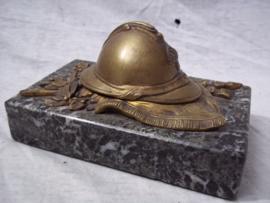 Press-papier, French miniature helmet on marble base. Franse miniatuurhelm met infanterie embleem in brons, liggend op vaandel gemonteerd op een marmeren voet, zeer decoratief.