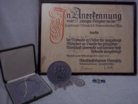 Duitse oorkonde met penning in doos, zilveren draagspeld met lint en rond speldje.  Für langjärige mitarbeit im Dienste der Pfälzischen Wirtschaft.  25 jaar. diameter penning 8 cm.