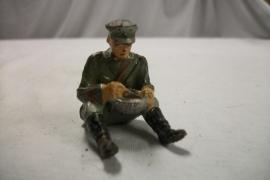 German soldier eating. Duits speelgoed soldaatje eet uit messtin