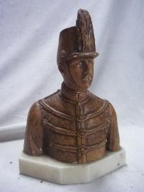 Statue of a Belgium soldier in ceremonial uniform.Buste van een belgische huzaar in dolman en met schako, beeldje is van gips met marmeren voet.
