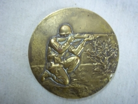 Military plaque shooting soldier, made by Drago.Franse penning met daarop een schietende soldaat, brons, gemaakt bij Drago.