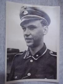 Duitse persfoto van een SS onder-officier van Leibstandarte Adolf Hitler LSAH. 18 bij 12,5 cm. met persbureau stempel achterop. lint van Ostfrontmedaille.