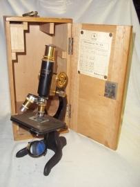 Microscope. Bronzen Microscoop in kist 1931, met enkele lensjes, met maker