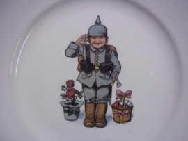 German humoristic plate a child dressed in a German uniform with spike helmet, made by VILLEROY and BOCH in Mettlach.Duits wandbord met militaire afbeelding kind in Duits uniform met pickelhaube, TOP staat.