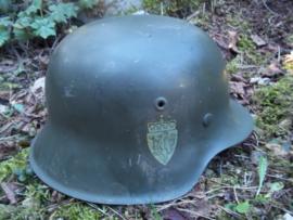 Noorse helm, Duits model 1942 met de twee decals van Noorwegen. Dit soort helmen zijn nu vrij zeldzaam, omdat vele omgebouwd zijn tot Duitse helmen, de 2 originele decals maken deze helm uniek, Model 42.