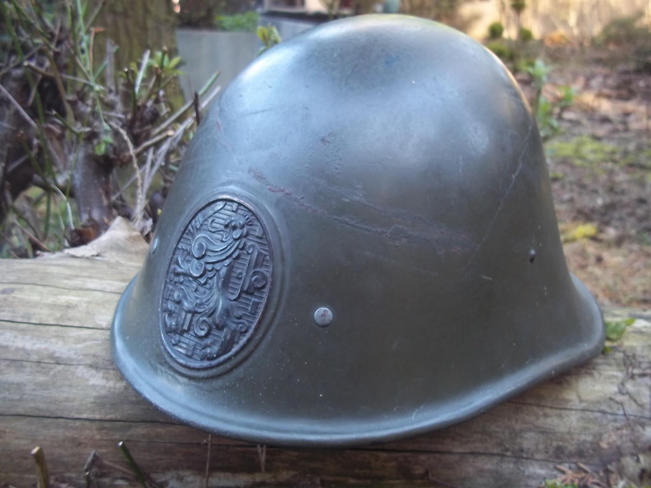 Nederlandse helm Model 1934 gedragen staat.