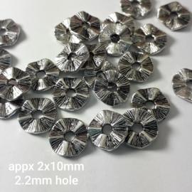 M 007: Spacer Gehobbeld Zilverkleur, ca 2x10mm (gat: 2,2mm)