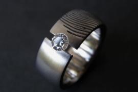 Titanium ring met openzetting en witte steen.