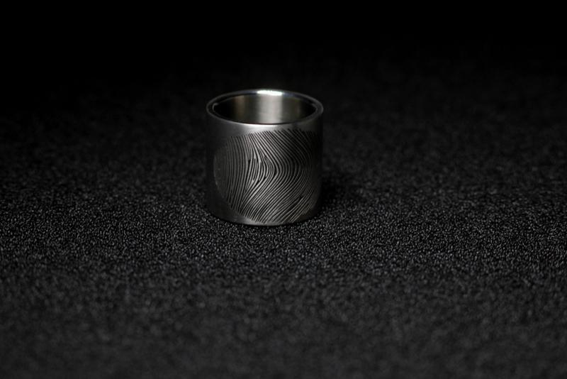 Titanium ring extra breed met een vingerafdruk op ware grote.