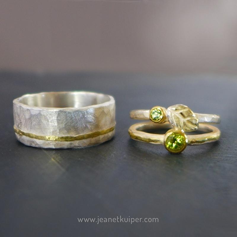 trouwringen met 18k gouden bandjes, twee peridots en een gouden blaadje