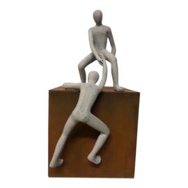 sculptuur man helpende hand op cortenstaal kubus