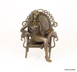 Bronzen beeld vrouw in pauwstoel