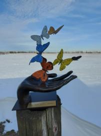 Bronzen hand met gekleurde vlinders