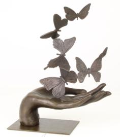 Zes bronzen vlinders in een hand