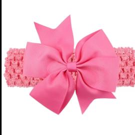 Gehaakte donker roze haarband met strik.