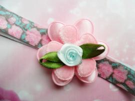 Smalle roze/groene baby haarband met bloem.