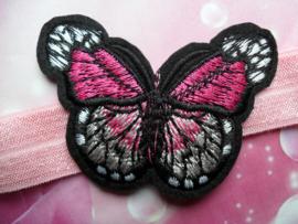 Smalle roze baby haarband met vlinder.