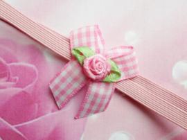Voor de allerkleinste super smal roze haarbandje met geruit strikje.