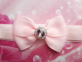 Smalle roze baby haarband met strikje en strass.