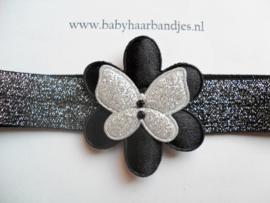 Smalle zwart/zilveren baby haarband met bloem en vlindertje.
