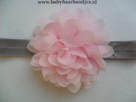 Smalle grijze baby haarband met roze toef.