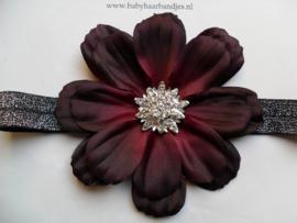 Smalle zwart/zilveren baby haarband met grote bloem.