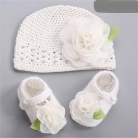 Gehaakt wit baby mutsje met bloem en slofjes.