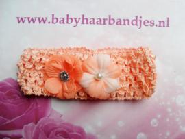 Gehaakte oranje haarband met  bloemetjes.