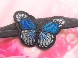 Smal zwart baby haarbandje met blauwe vlinder.