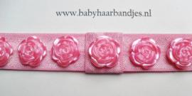 Smalle donker roze baby haarband met roosjes.