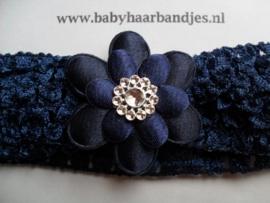 Gehaakte donker blauwe haarband met bloem.